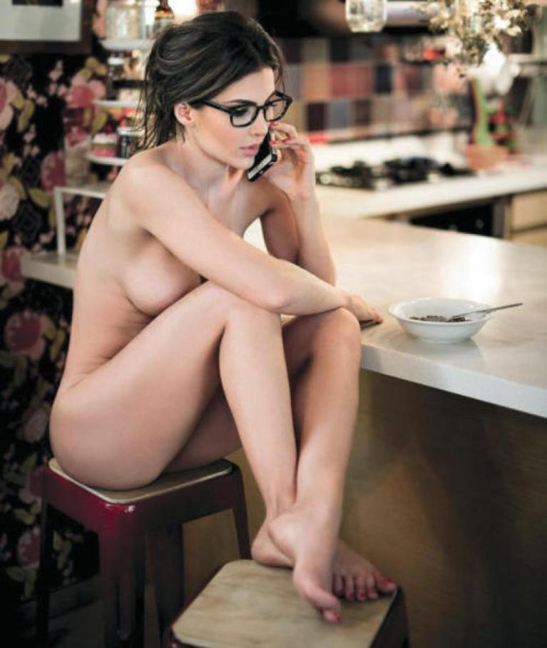 Naked woman on a stool with a mobile phone