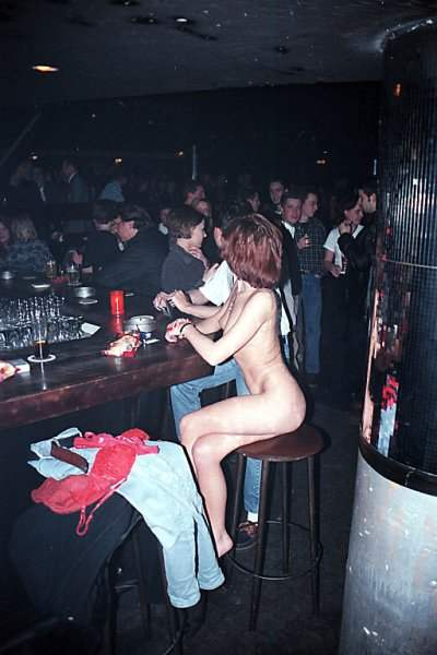 Woman sitting naked at a bar
