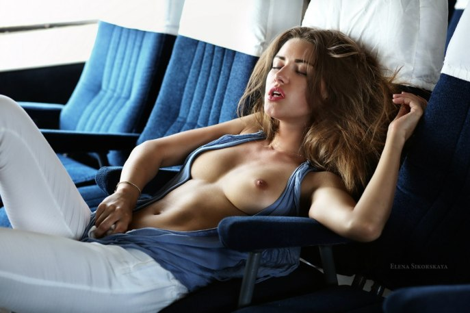Beautiful woman unzipping her top on a plane