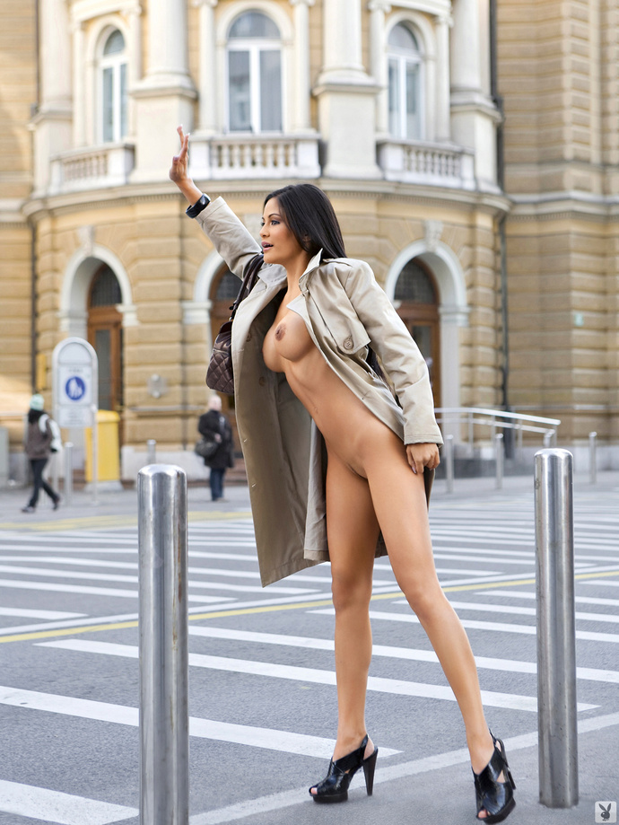 Woman in only a coat hailing a cab