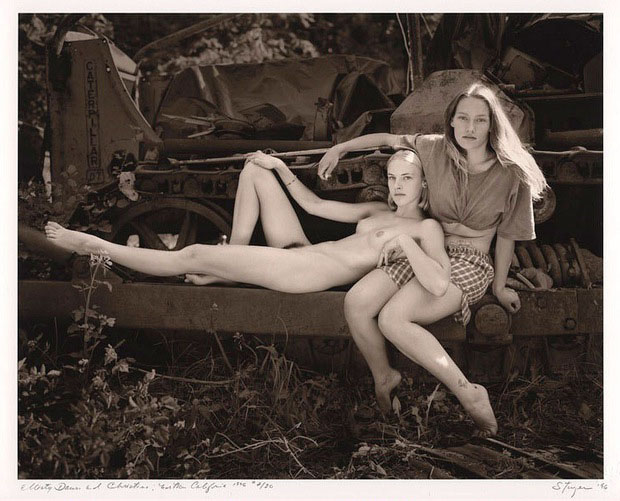 Naked woman across clothed woman