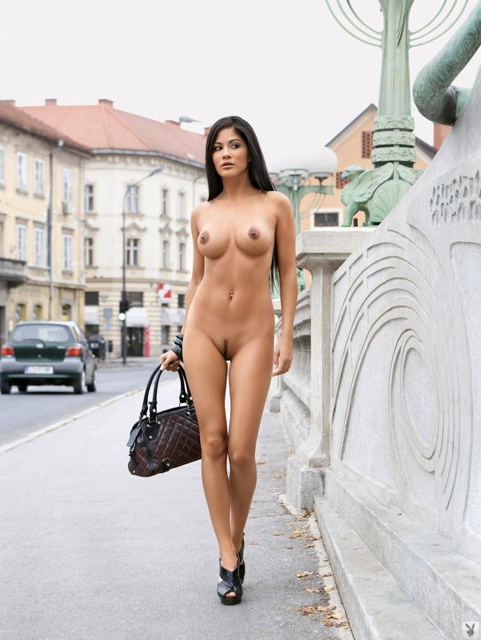 Naked woman carrying a handbag down the street
