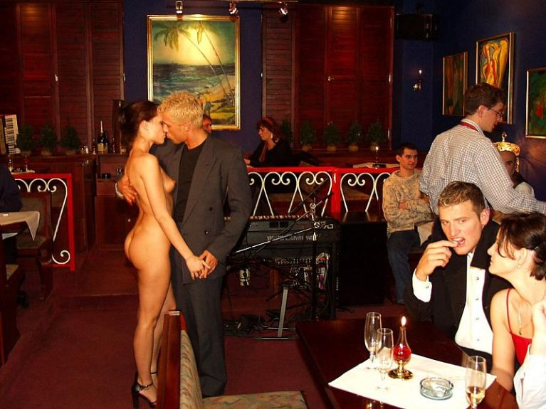 Naked woman with a clothed man in a restaurant