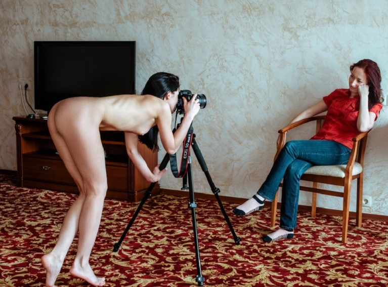 Naked woman photographing a clothed woman