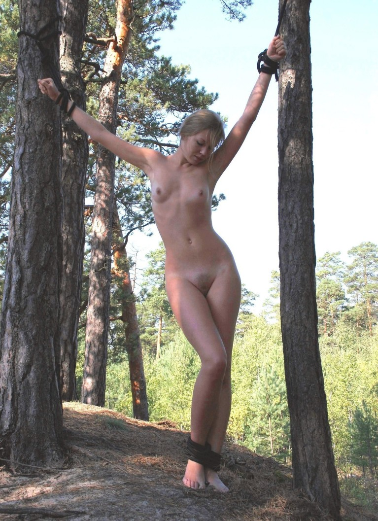 Naked woman tied between two trees