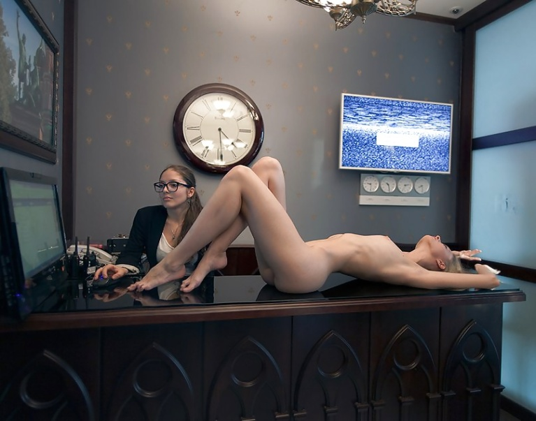 Naked woman on desk in front of clothed woman