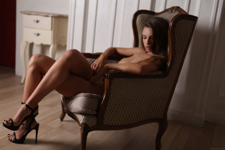 Naked woman in heels in an armchair