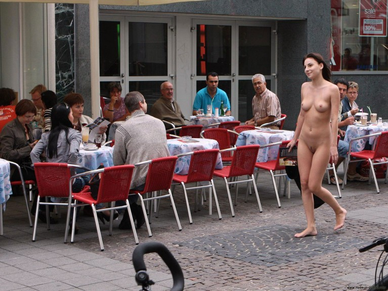 Naked woman walking past a restaurant