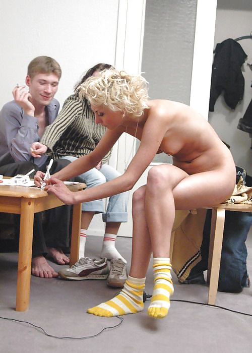 Woman naked except for socks signing a piece of paper