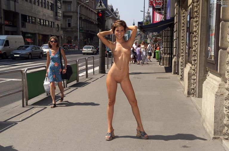 Naked woman standing in a city street