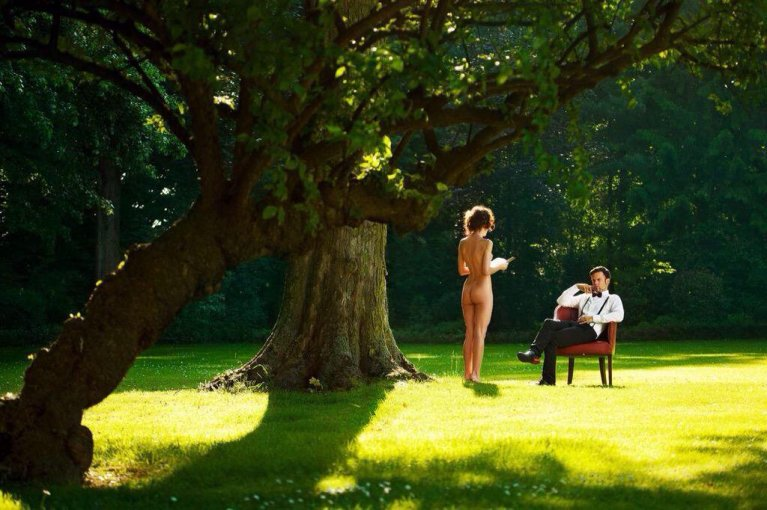 Naked woman reading outdoors to clothed man