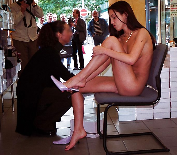 Naked woman putting on a shoe