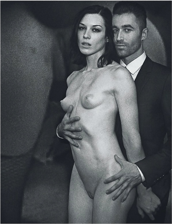 Naked woman held by smartly dressed man