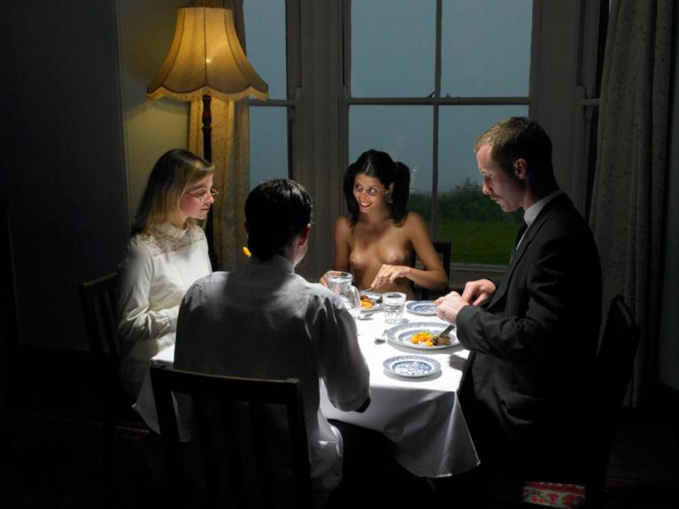 Naked woman eating dinner with clothed men and women