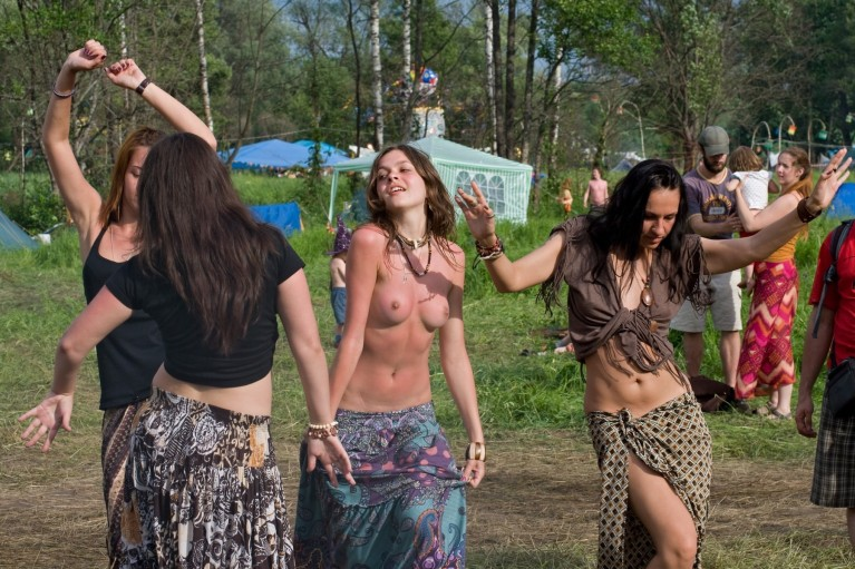 Topless girl dancing at a festival