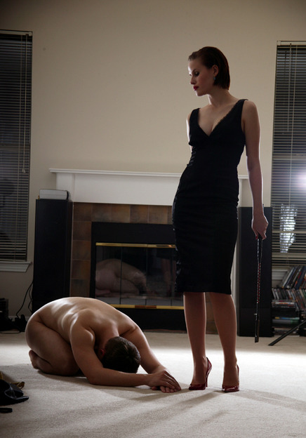 Naked man bowing before woman in a black dress