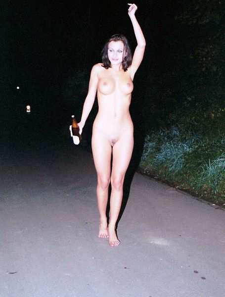 Naked woman walking down a street at night