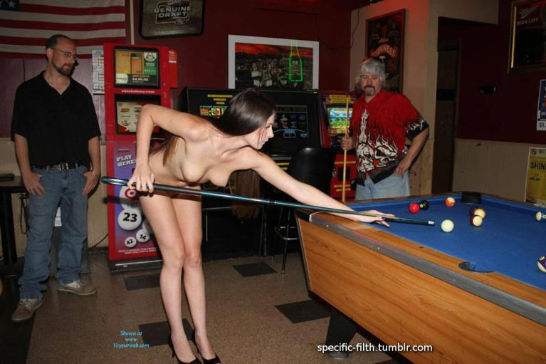 Naked woman playing pool