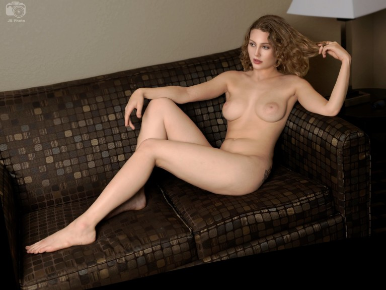 Naked woman reclining on a couch