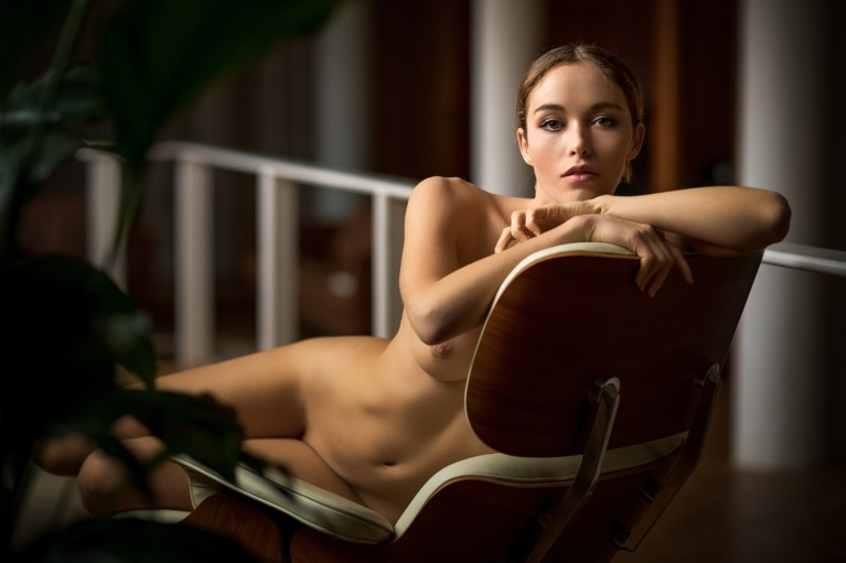 Nude woman on a laid back chair