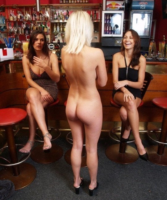 Naked woman at a bar with two clothed women