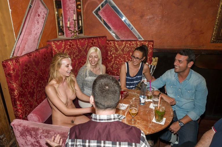 Naked woman at a restaurant table with clothed group