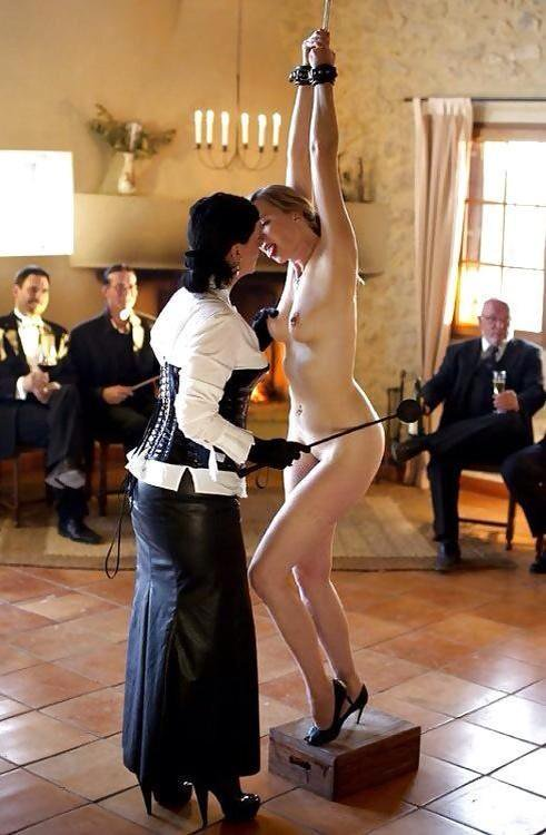 Clothed woman with riding whip fondling naked woman in handcuffs