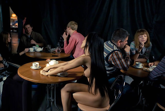 Naked woman at a cafe table